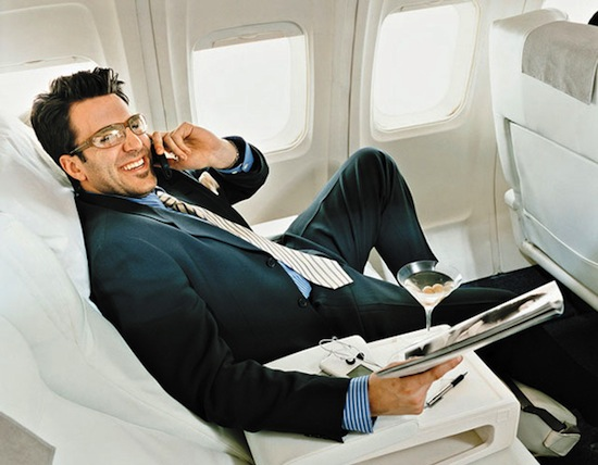Sitting in an aircraft wearing glasses and holding a magazine
