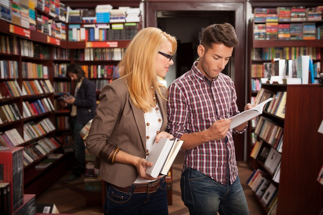 young caucasian people reading a book in a library